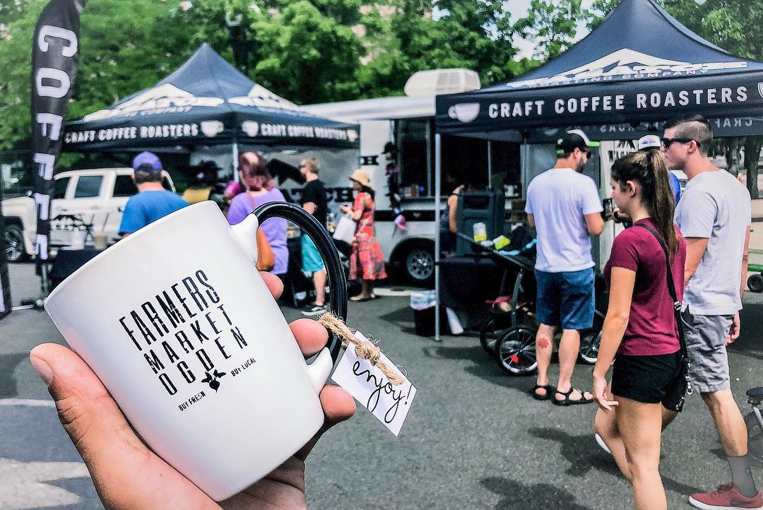 an image of a farmers market coffee mug being held up in front of Wasatch Roasting Compan's booth