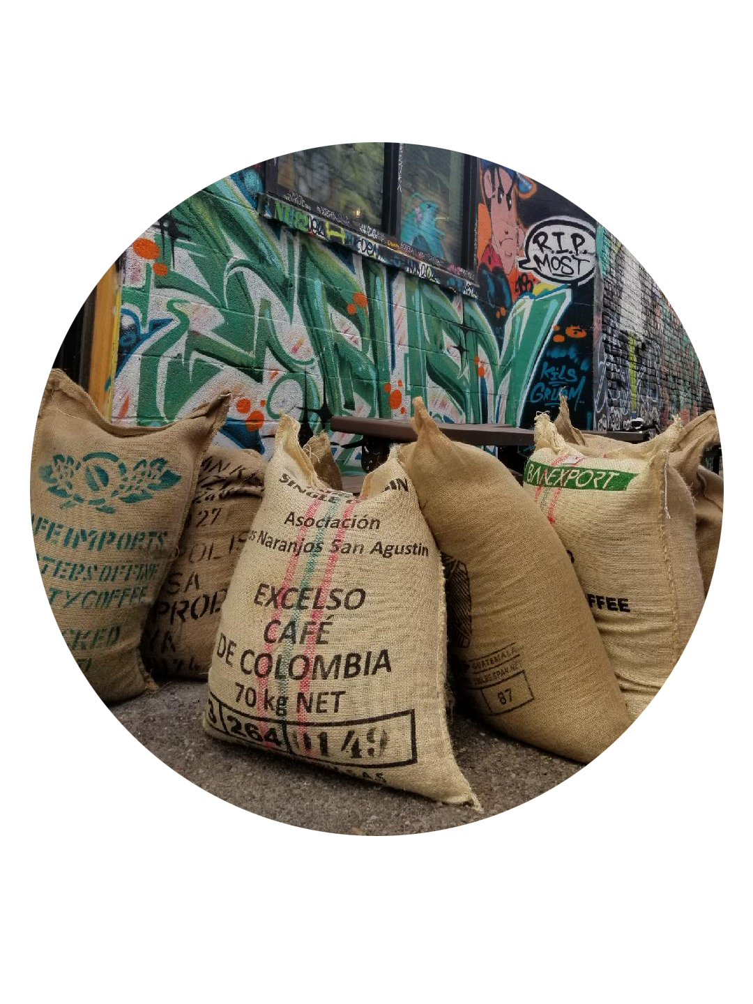 image of large burlap sacks of coffee in front of a graffiti covered wall